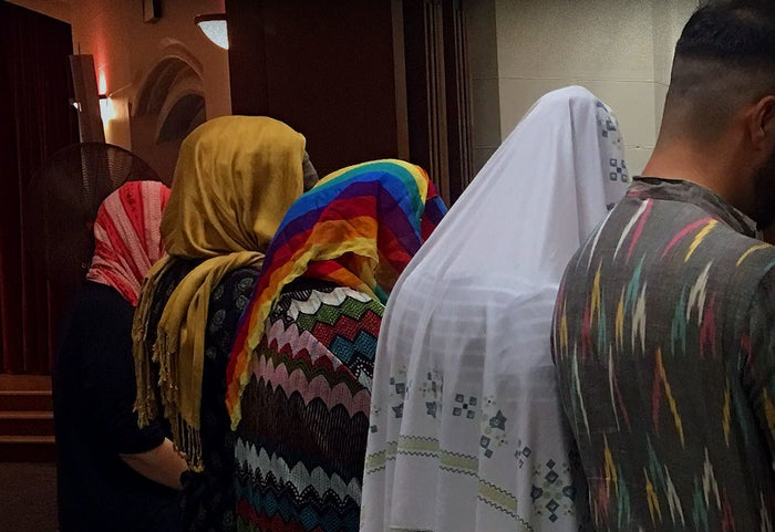 LGBT Muslims and friends pray behind a woman, one of the many unconventional features of an LGBT iftar this month in Minneapolis.