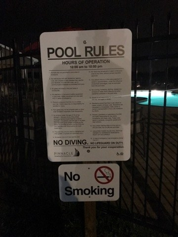 "A list of rules by the pool states that ""duly appropriate attire must be worn at all times. No cut offs."""