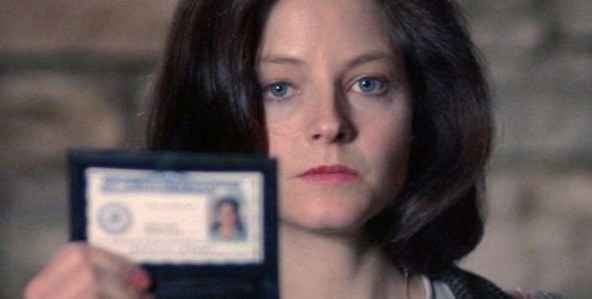 A screenshot of Jodie as Clarice holding her FBI ID towards the camera