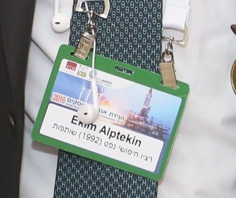 A detail of the badge that Alptekin can be seen wearing at the Israel Energy and Business Convention identifies him as affiliated with Ratio Oil Exploration, which is written in Hebrew.