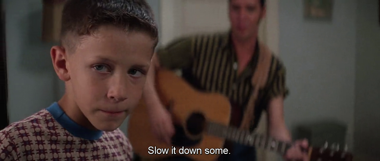 """A screenshot from """"Forrest Gump"""" of a young Forrest with blurred Elvis Presley in the background holding a guitar saying """"Slow it down some"""""""