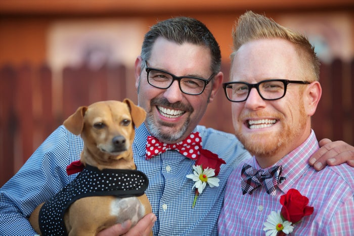 A cheerful married gay couple outdoors with dog.
