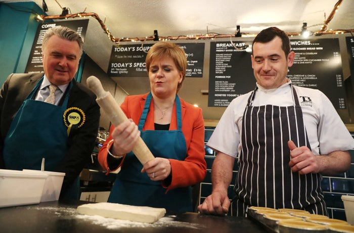 Nicola Sturgeon holds a rolling pin as she and the SNP's local candidate John Nicolson (left) make haggis pies with Table 13 Express co-owner Iain Murphy on a campaign visit to the café in Kirkintilloch, East Dunbartonshire.