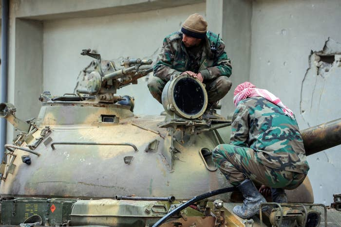 Members of the Syrian government forces sit over the turret of a tank.