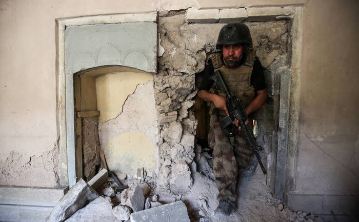 A member of the Iraqi Counter-Terrorism Service (CTS) walks through the rubble and broken wall of a damaged building.