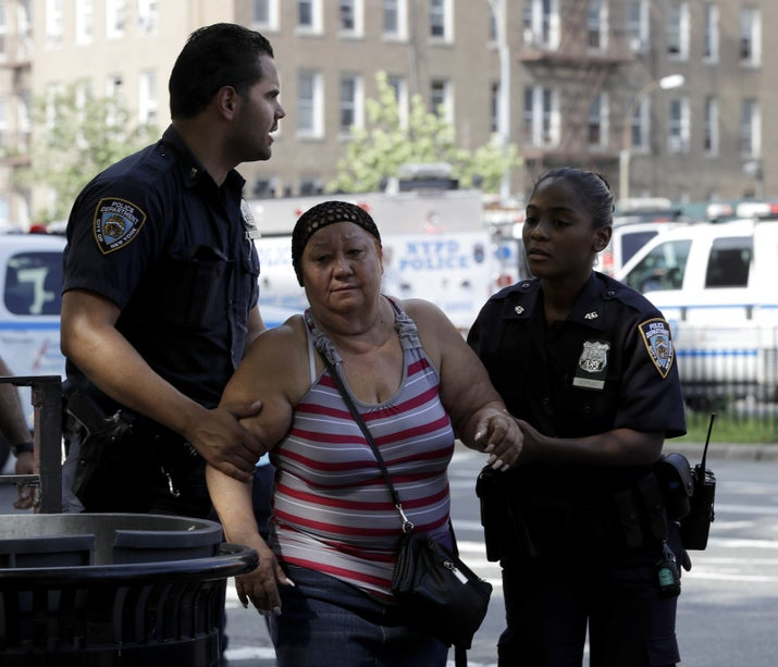 A woman is escorted by officers near the Bronx Lebanon Hospital Friday.
