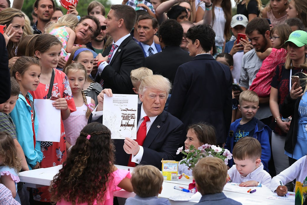 President Trump holds up the coloring sheet he wrote on while joining children at a craft table during the 139th Easter Egg Roll on the White House's South Lawn on April 17, 2017.