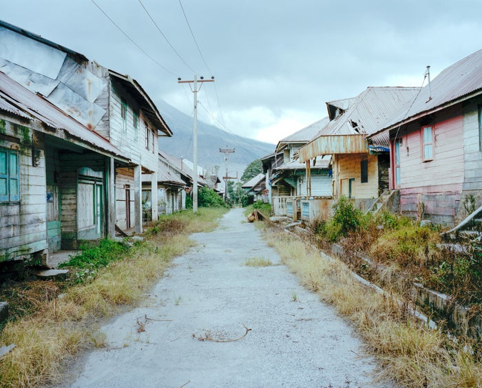 Abandoned houses line a road in Sukanalu village near the base of Mount Sinabung.