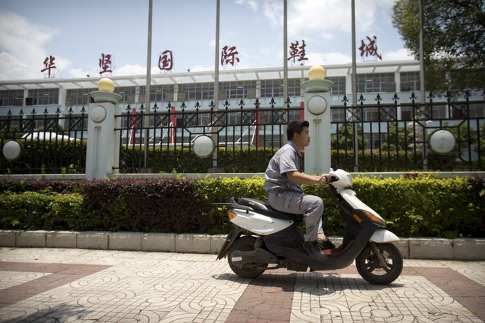 A man rides a scooter outside of a Huajian Group shoe factory in Ganzhou Tuesday.