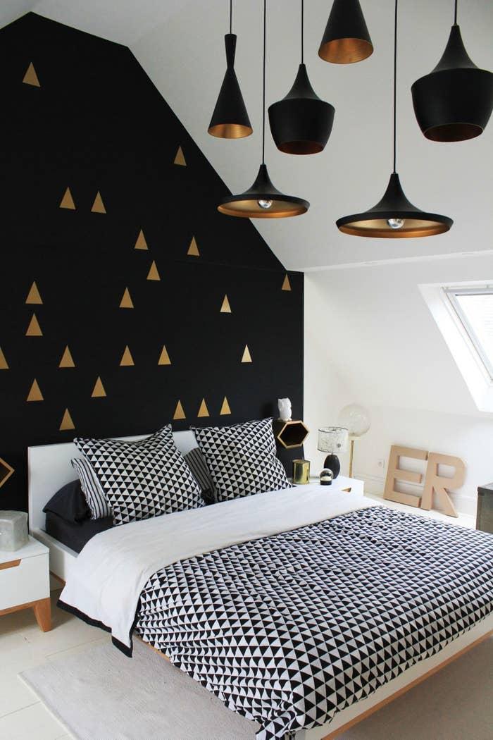 Pintar figuras geométricas metalizadas sobre una pared negra, y decorar el lugar con toques dorados, le dará un toque goth glam a tu habitación.