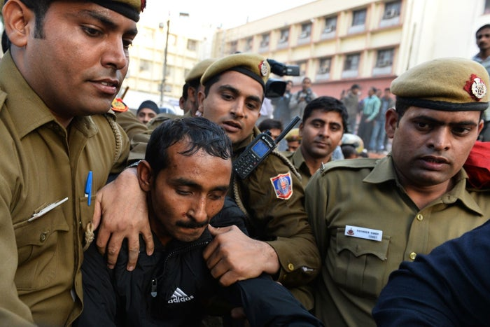 Indian police escort Uber taxi driver and accused rapist Shiv Kumar Yadav following his court appearance in New Delhi on Dec. 8, 2014. Delhi's government on Dec. 8 banned Uber from operating in the Indian capital after a passenger accused one of its drivers of rape.