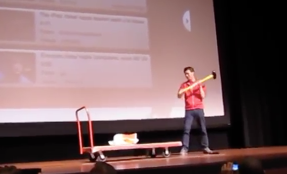 Heiferman sledgehammering an iPad to encourage people to spend time offline.