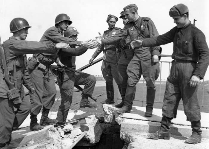 US troops of the 69th Infantry Division shake hands with Soviet troops in a staged photo on the wrecked bridge over the Elbe in Torgau, Germany, to mark the previous day's linkup between US and Soviet forces on April 26, 1945.