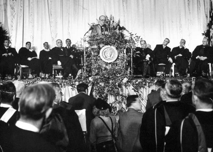 """President Harry S. Truman (to the left of the podium) listens on as British Prime Minister Winston Churchill makes a speech about the Communist threat, in which he said his famous line: """"From Stettin in the Baltic to Trieste in the Adriatic, an Iron Curtain has descended across the continent."""""""