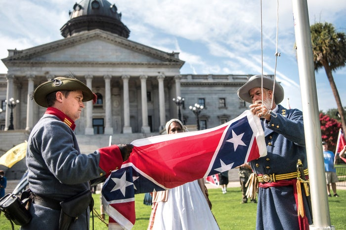 Two men raise a Confederate flag on the grounds of the South Carolina Statehouse in Columbia on July 10. The protest marked the two-year anniversary of the removal of the controversial flag from all government posts.