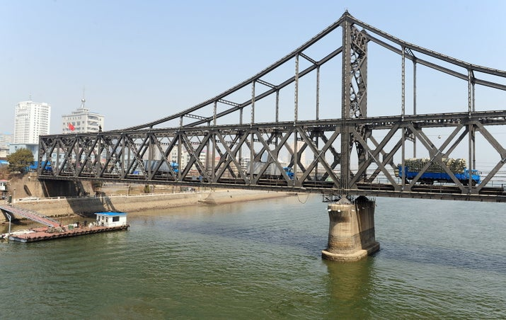Trucks cross the bridge across the Yalu river from Dandong into North Korea.