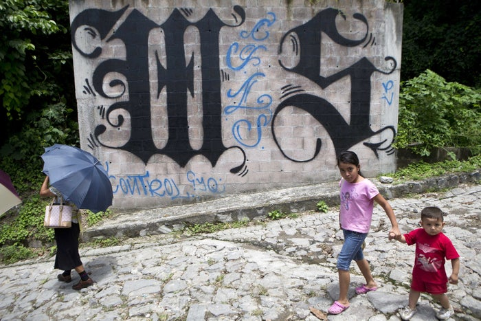 A family walks by a wall covered by a symbol from the Mara Salvatrucha, of MS-13 gang in Ilopango, El Salvador.