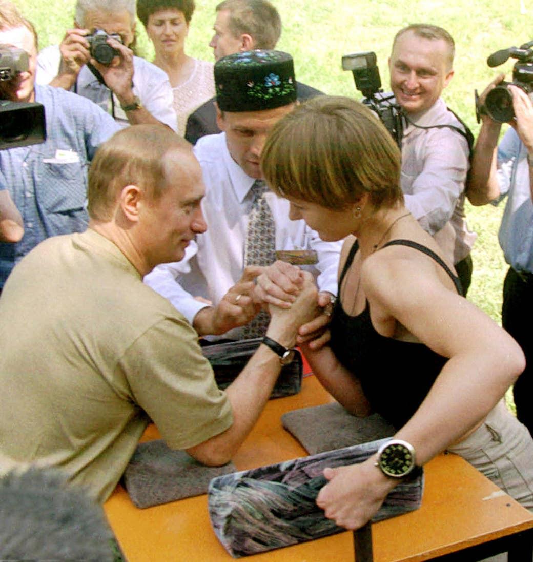 Putin arm wrestles a woman during mid-summer festivities in Kazan in the Tatarstan region of Russia on June 25, 2000.