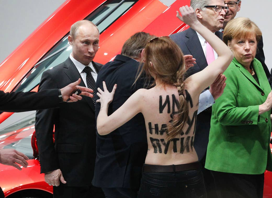 Putin and German Chancellor Angela Merkel react as an activist from the Ukrainian womens' rights group Femen protests during a visit to an industrial exhibition in Hannover, Germany, on April 8, 2013.