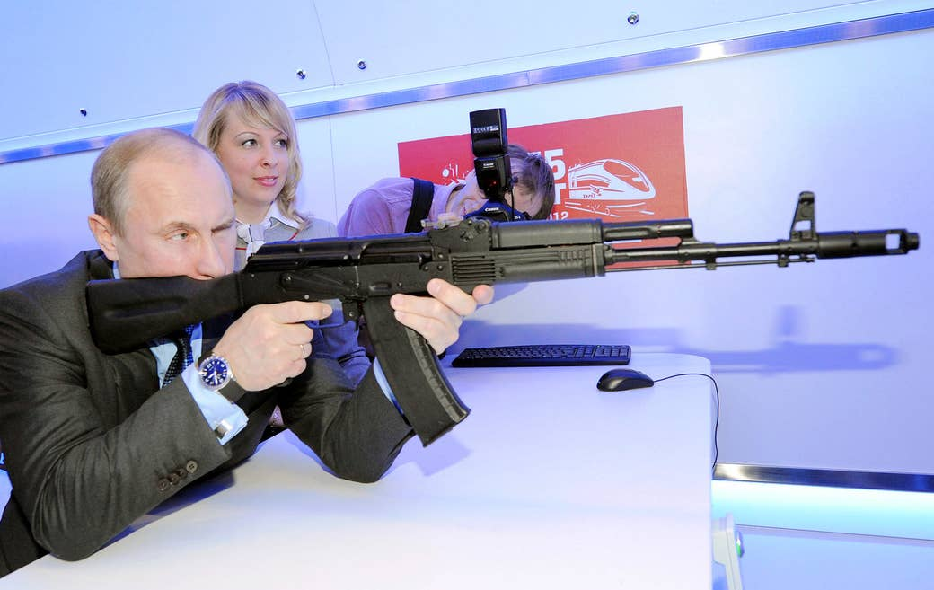 Putin takes aim with a replica of a Kalashnikov assault rifle in Moscow on April 26, 2012.