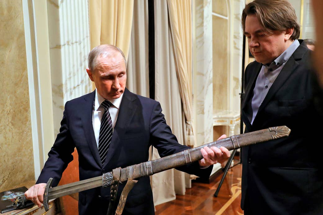 Putin holds a sword during a meeting with the crew of the film Viking on Dec. 30, 2016, in Moscow. Konstantin Ernst, the film's producer and director general of Channel One Russia, looks on.