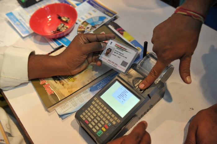 An Indian visitor gives a thumb impression to withdraw money from his bank account with his Aadhaar card in January 2017.