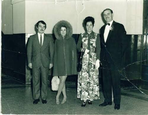 Esta foto se tomó en 1972, y muestra a cuatro invitados en una boda. Solo cuatro invitados posando para una foto en una boda. Salvo que... ¿qué es eso entre las piernas del hombre en la derecha?