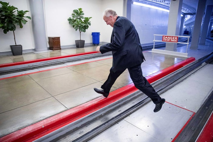 Republican Sen. Jerry Moran jumps the tracks of the Senate subway on Capitol Hill to get around a large gathering of reporters in Washington, DC, on July 18. On Monday, Moran announced his opposition to the Senate health care bill, effectively killing its chances of passing.