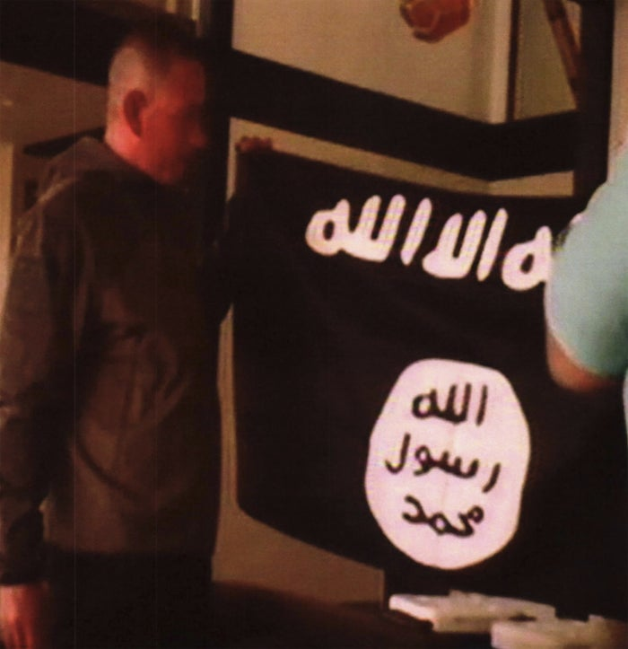 In this image taken from FBI video and provided by the US Attorney's Office in Hawaii, Army Sgt. 1st Class Ikaika Kang holds an Islamic State group flag after allegedly pledging allegiance to the group at a house in Honolulu on July 8.