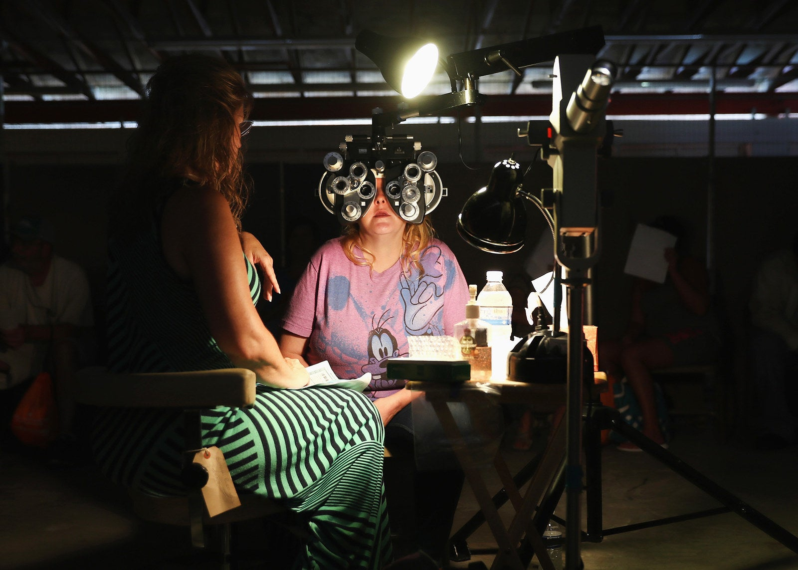 A volunteer checks a patient's vision at the RAM clinic in Wise on July 21.