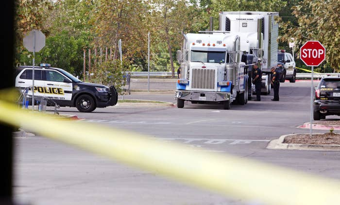 San Antonio police officers investigate the scene where eight people were found dead in a tractor-trailer.