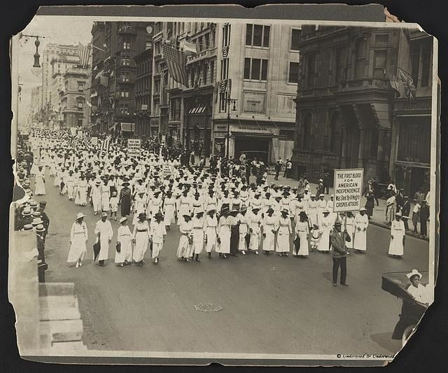 "A marcher on Fifth Avenue holds a sign that reads ""The first blood for American independence was shed by a Negro: Crispus Attucks."""
