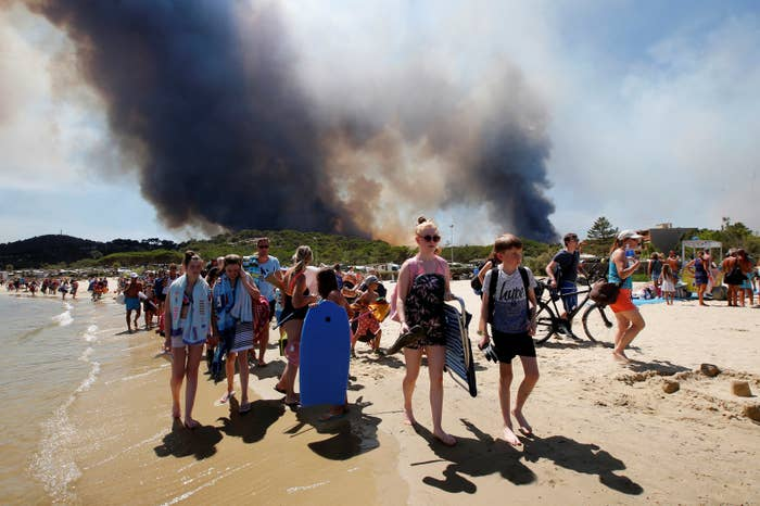 Tourists evacuate a beach Wednesday in Bormes-les-Mimosas, France.