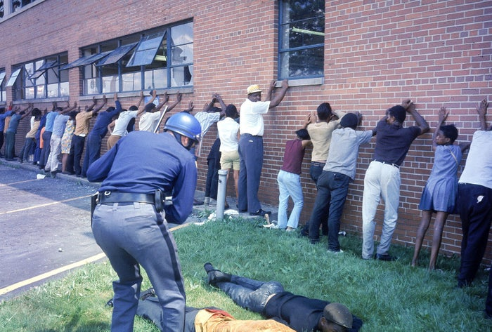 A Detroit police officer lines up people as riots ensue in late July 1967.
