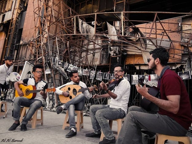 During the festival, four young local musicians performed on the steps of the library. In the background, photographs of life and people in Mosul, taken by students at the university, hung on a clothing line.