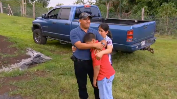Andres Magana Ortiz hugs his two youngest children.