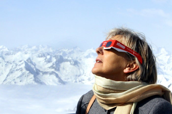 A woman observes a partial solar eclipse from Midi peak in the southwestern Pyrenees on March 20, 2015 .