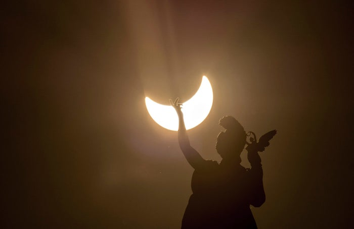 A partial solar eclipse above a statue on the roof of the Austrian Art History Museum in Vienna on March 20, 2015.