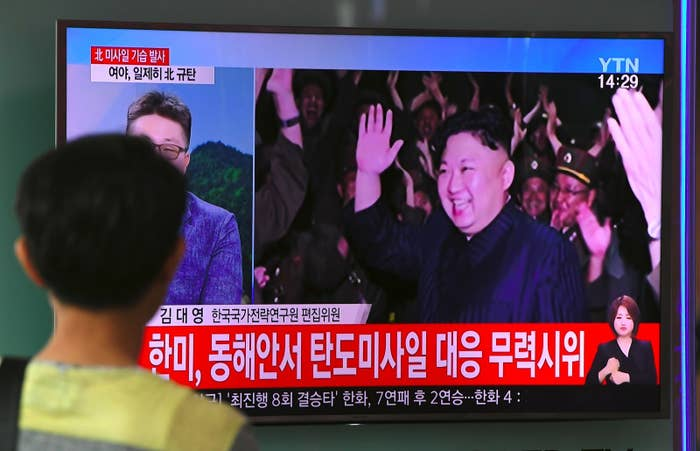 A television screen shows video footage of North Korean leader Kim Jong-Un celebrating his country's latest test launch of an intercontinental ballistic missile.