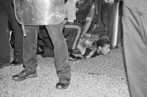 A protestor is forced to the ground and detained by police: