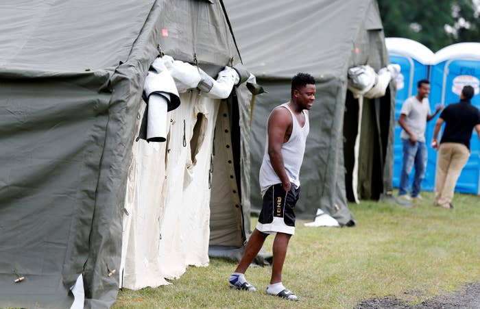 A Haitian refugee walks from his tent.