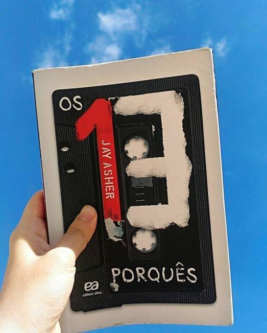 """O livro conta a história dos 13 motivos que levaram a jovem Hannah Baker ao suicídio. Em meio a essa trágica história, o leitor toma uma surra de realidade sobre a vida e os possíveis problemas do jovem millenial. Tanta gente lê e pensa """"nossa, muito eu"""" que o livro vendeu milhões de cópias e inspirou uma série da Netflix."""