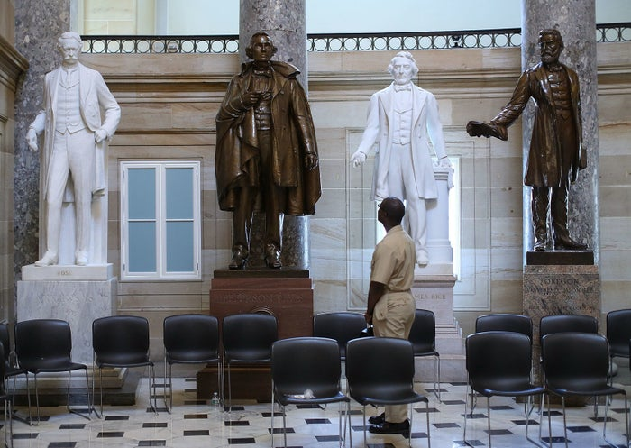 US Navy Lt. William Edmund Newsome looks at a bronze statue of Confederate President Jefferson Davis that stands inside of Statuary Hall at the US Capitol.