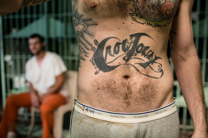 Justin Wright in Coshocton County Jail, which is severely overcrowded. He has tattooed his torso with the town's nickname, Crowtown, and the county's area code, 740.