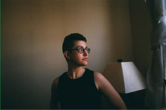 Dom, a nonbinary person with short black hair, wearing a black tank top.
