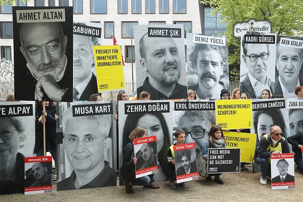 Supporters hold photos of jailed journalists in front of the Turkish Embassy in Berlin.