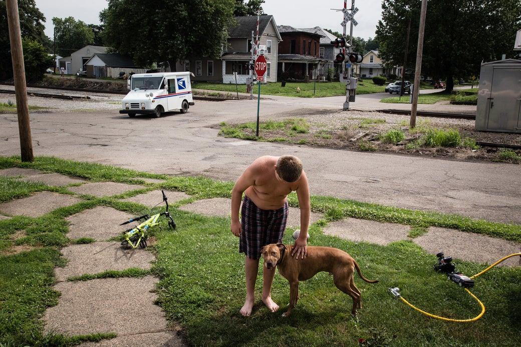Jordan Lanham, 11, pets his dog outside his house.