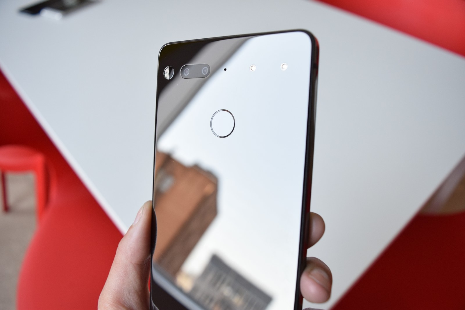 "The first thing you'll notice is that it's stunning. The phone is made of titanium (which, apparently, is stronger than the aluminum in the Pixel and iPhone) and ceramic. Most notably, it doesn't have a camera bump. It lies completely flat, which reduces any scratch risk for the camera's lens. And I love that it's logo-less. In fact, that was a design point for Rubin: ""On the phone, there's no branding. It's not a NASCAR. It doesn't have a carrier brand. It doesn't have our brand. Doesn't have the retail channels' brand. Customers spend their hard-earned money on this. We want it to become their product.""The black version has a mirrored back that's incredibly shiny and smooth. It also attracts a lot of fingerprints. Speaking of which, there's a fingerprint sensor in the back to unlock your phone.It doesn't feel like it'll slip out of your hand, though. There are matte edges around the display that provide just the right amount of friction (and help cellular signals go through the chassis)."