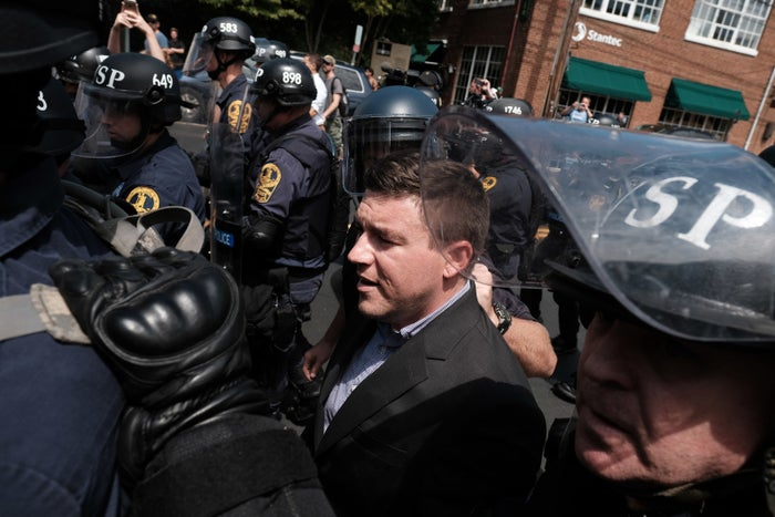 Unite the Right rally organizer Jason Kessler is escorted by police after attempting to speak at a press conference in front of Charlottesville City Hall.