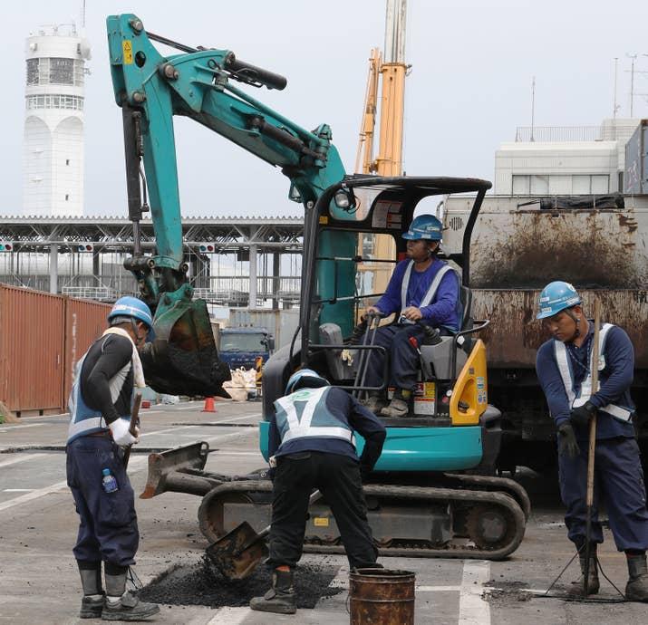 ヒアリが発見された横浜港の本牧ふ頭で、定着防止のためコンテナターミナルの舗装の隙間をアスファルトで埋める作業員
